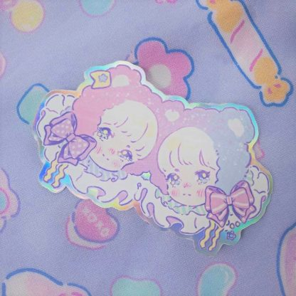 pastel holographic sticker of twin anime boys with teddy bear ears and ribbons.