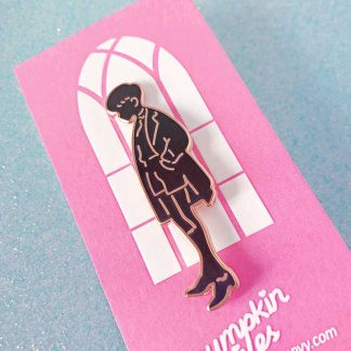 black colored enamel pin with gold metal of a school boy
