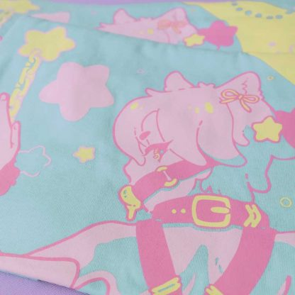 clooseup photo of a pastel blue cotton tshirt with a screen-print illustration of a magical neko boy with handcuffs and gag, and a moon in the background