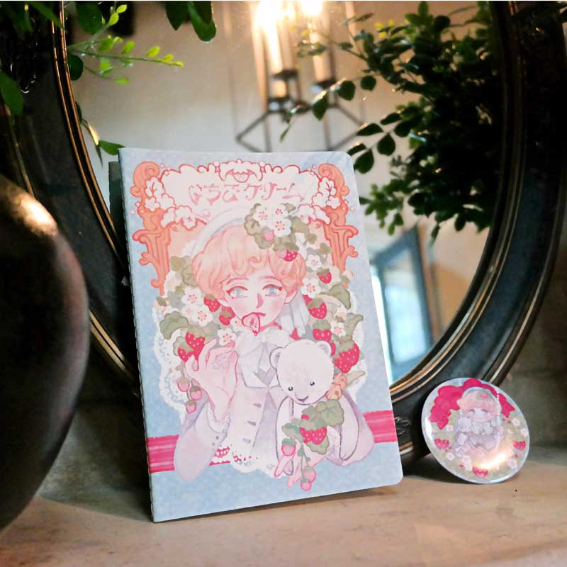 strawberry anime boy with shojo style illustration on the a pin back button and sketchbook