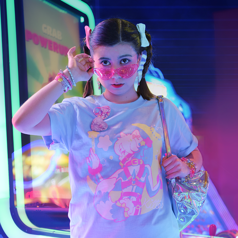 model wearing a pastel blue cotton tshirt with a screen-print illustration of a magical neko boy with handcuffs and gag, and a moon in the background