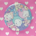 a button in pastel color with sleeping boys with their soft plushies