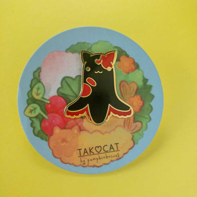 a hard enamel pin of octopus cat on a bento backing